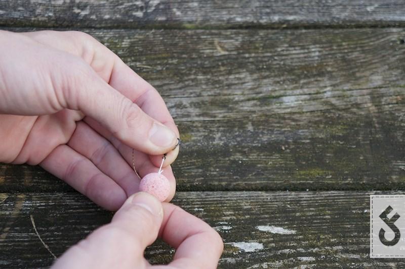 Monteer vervolgens je boilie met behulp van bait floss op de micro swivel. Knip de overtollige bait flos af en laat ca. 1 cm over. Brand dit nu weg met een aansteker en blob het met de achterkant van je aansteker.