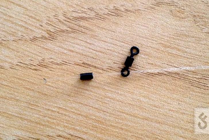 Knip een stuk stiff rigmateriaal af en brand het uiteinde heel even met een aansteker. Druk het gebrande stukje plat tegen de aansteker aan. Rijg nu de tube en ring swivel aan het onderlijnmateriaal.