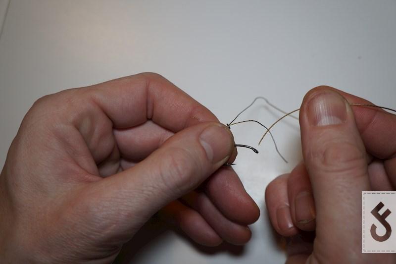 Plaats het einde van lus op de shank tegenover de weerhaak. Haal nu zowel het coated als gestripte gedeelte door het oog van de naald van achter naar voren.