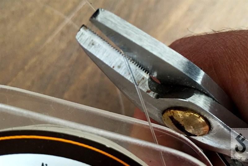 Knip een stuk fluorocarbon af van ongeveer 20 centimeter. Knip de lijn schuin af zodat je hem gemakkelijk door het oog van je haak krijgt.