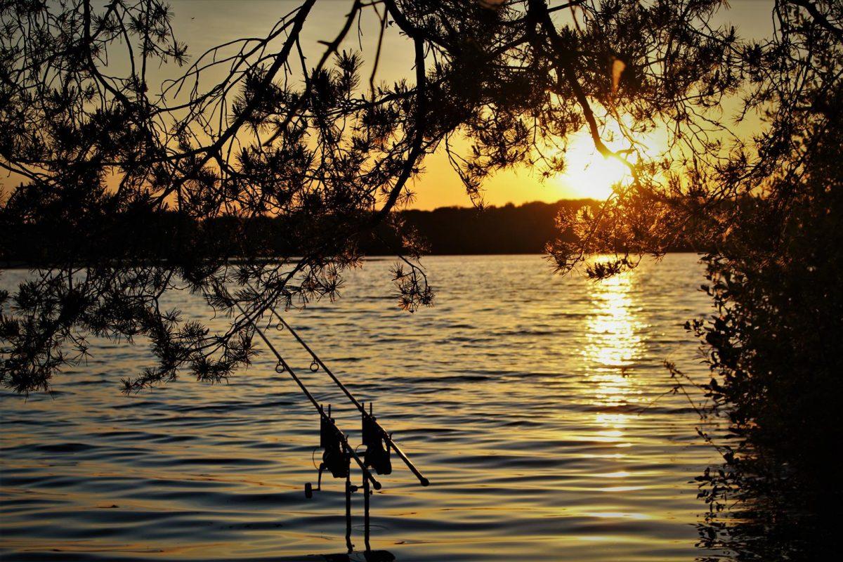 De zon gaat onder terwijl Ian vist op het water waar de Grote Schub zwemt